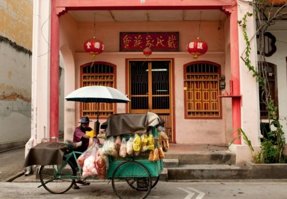 A food vendor walks past a traditional Chinese shopfront.