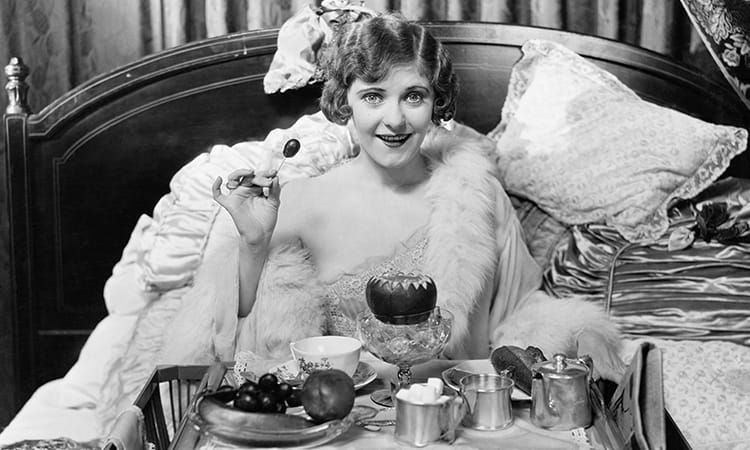 Black and White Photo of Woman eating in bed