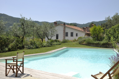 Vacker nybyggd villa med pool omgiven av den gröna landsbygden i Toscana