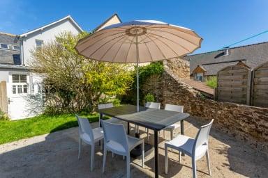 Terrasse avec table à manger, parasol et jardinet