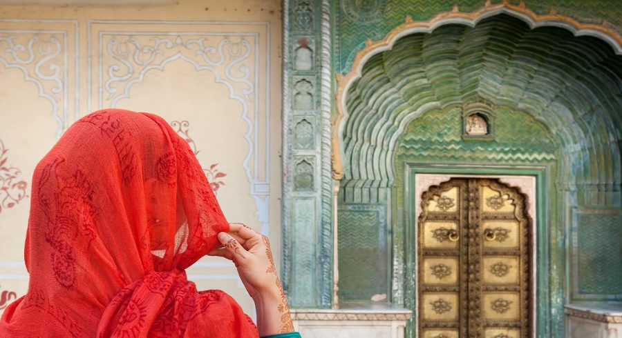 Enchanting Travels India Tours Jaipur Woman in red scarf looking at green gate door in City Palace