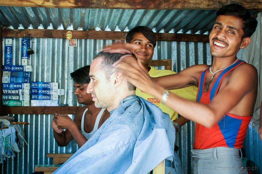 Friseur gibt einem Touristen in Indien eine Kopfmassage