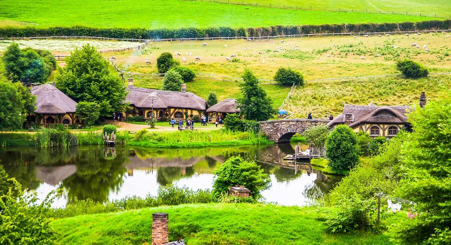 Enchanting Travels New Zealand Tours Summer river village in Shire, Hobbiton, New Zealand. Hobbit houses at river in Hobbiton, New Zealand