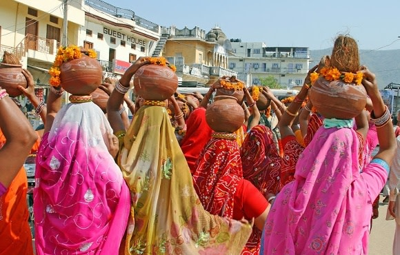 Frauen in bunter traditioneller Kleidung tragen Schüsseln auf ihren Köpfen, Indien