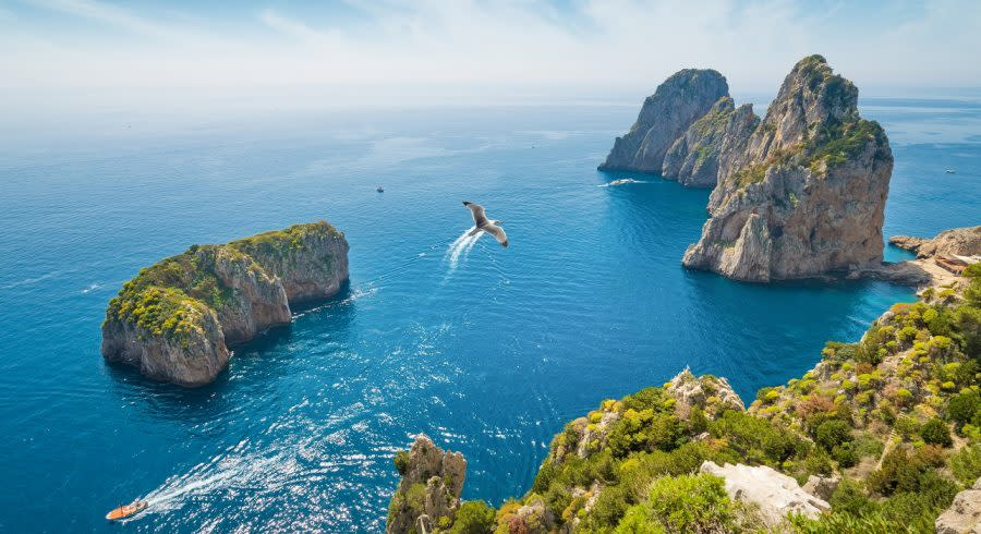 Enchanting Travels Italy Tours Aerial view of famous Faraglioni rocks from Capri island, Italy.