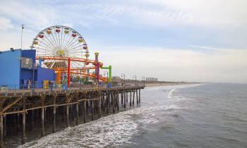 a close up of a pier next to a body of water with Santa Monica Pier in the background