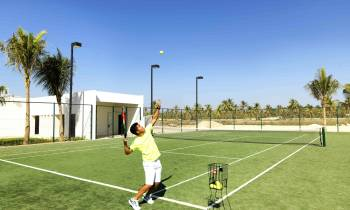 a man holding a football ball on a court with a racket