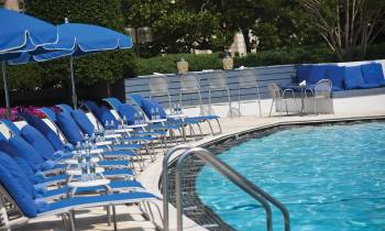 a row of lawn chairs sitting next to a pool of water