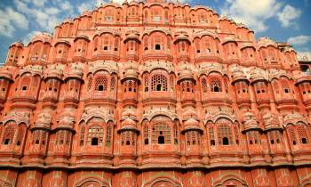 a large brick building with Hawa Mahal in the background