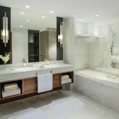 a white sink sitting under a large mirror