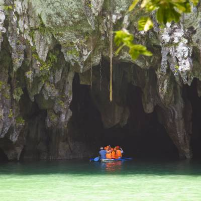 a boat sitting on top of a rock with Puerto Princesa Subterranean River National Park in the background