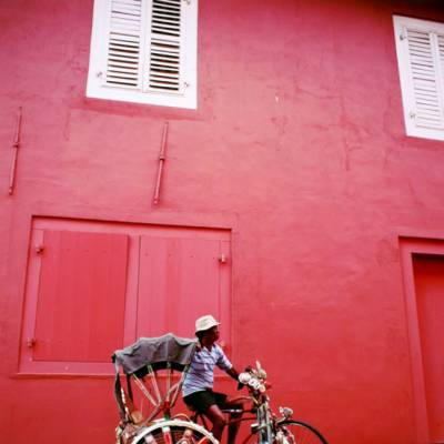 a red bicycle is parked on the side of a building