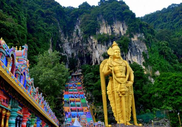 a group of people standing in front of Batu Caves
