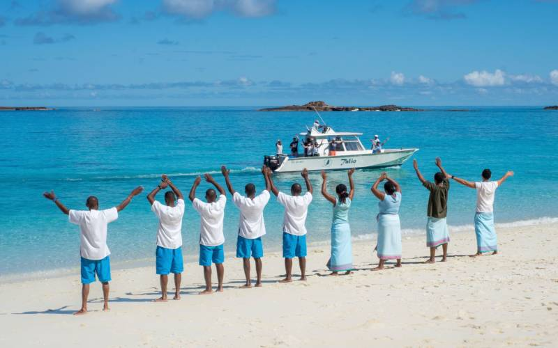 a group of people on a beach near a body of water