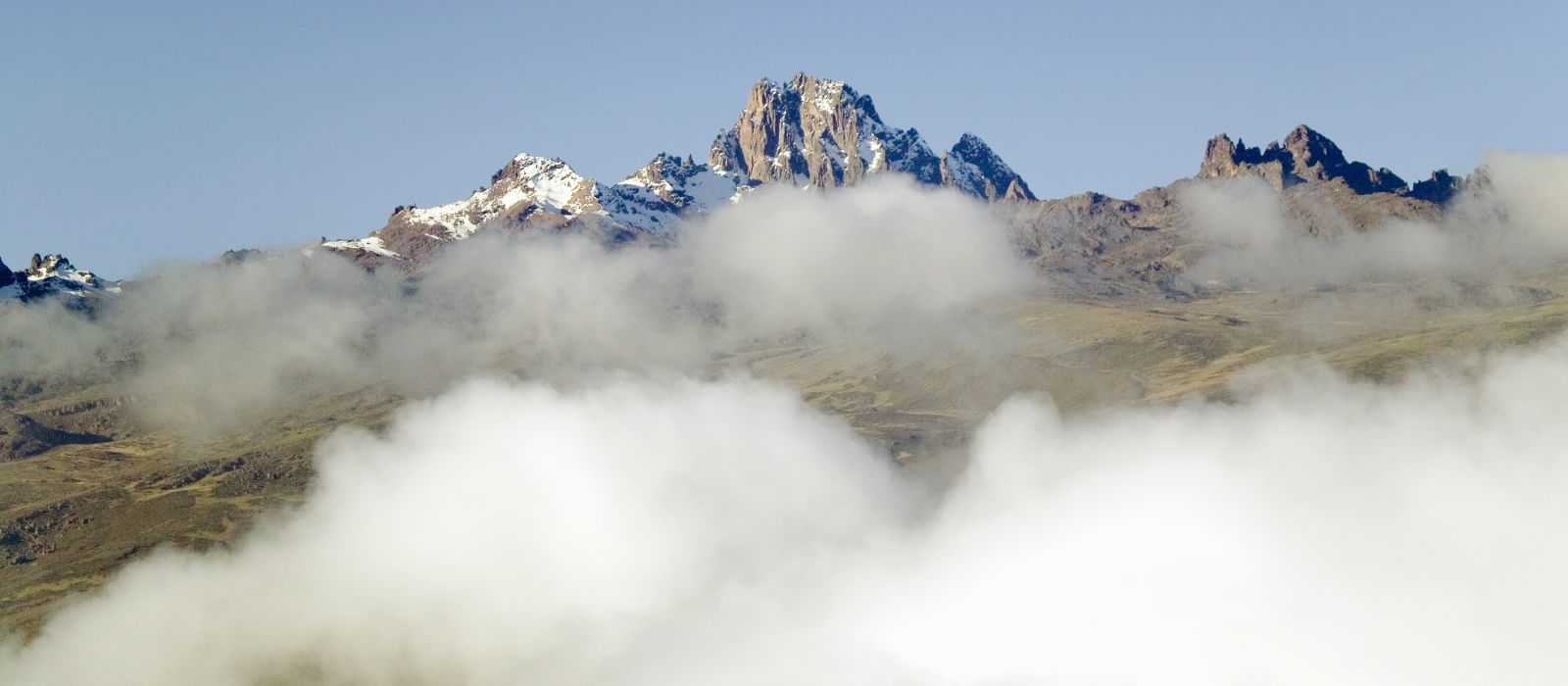 Aerial of Mount Kenya, Africa with snow and white puffy clouds in January