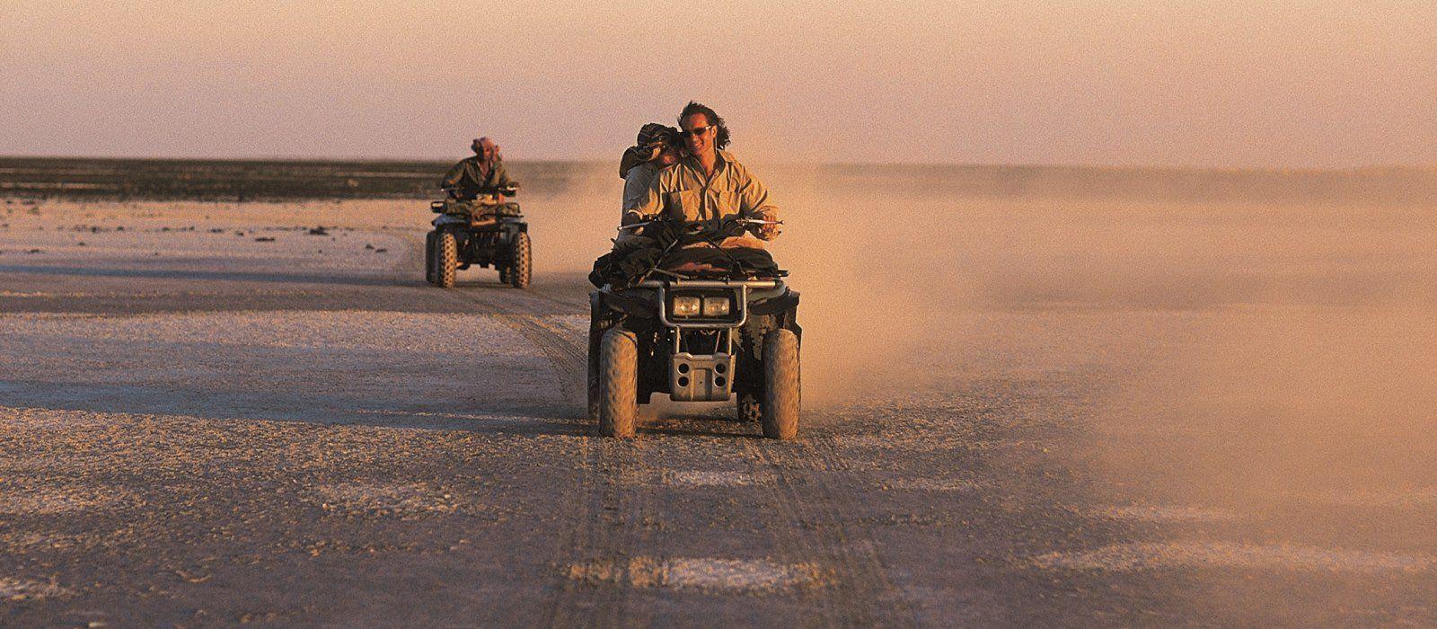 Zwei Quadbikes fahren hintereinander durch die Wüstenlandschaft