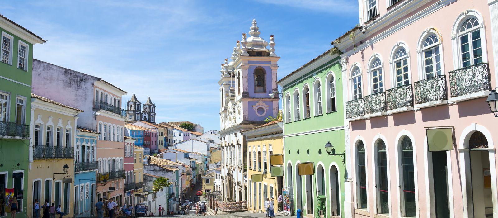Historic city center of Pelourinho features brightly lit skyline of colonial architecture on a broad cobblestone hill in Salvador, Brazil, South America