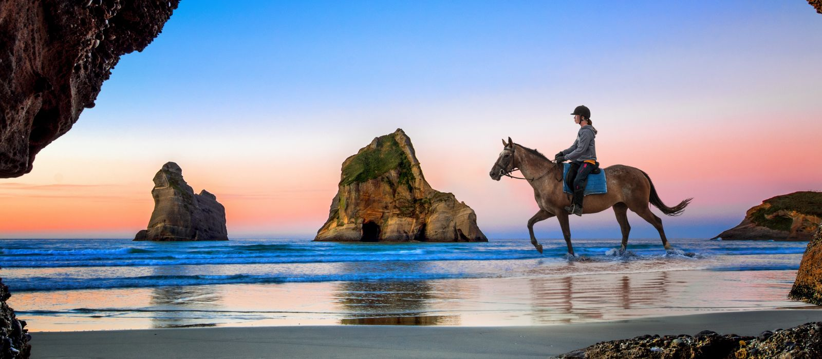 Cave of Wharariki Beach with horse rider, South new Zealand