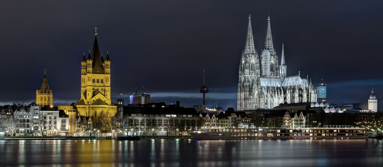 Illuminated buildings and cologne cathedral by rhine river in city at night, Germany, Europe