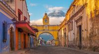 The colorful main street of Antigua City at sunrise with the famous yellow arch in the center and the active Agua volcano, Guatemala, Central America