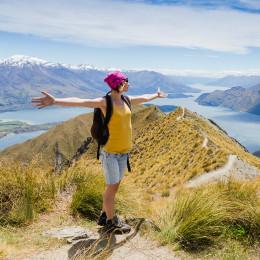 Junge Frau mit ausgestreckten Armen auf einem Berg in Neuseeland