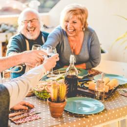 Gruppe älterer Menschen prostet sich an einem gedeckten Tisch ausgelassen mit Weingläsern zu