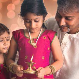 Girl holding a lamp on her hand celebrating Diwali