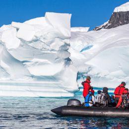 Enchanting Travels Antarctica Tours Boat full of tourists explore huge icebergs