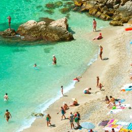 Enchanting Travels France Tours beach of the Cote d'Azur with tourists with sunbeds and umbrellas on the hot summer day