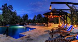 Pool der Kanha Earth Lodge in Indien bei Sonnenuntergang