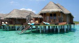 Außenansicht von reetgedeckten Villen auf Stelzen im türkisfarbenen Wasser der Malediven