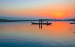 Enchanting Travels India Tours fisherman with his net and boat on the River Brahmaputra at Sunset