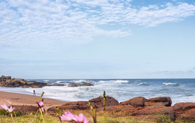 Raue Küste mit Leuchtturm und Brandung