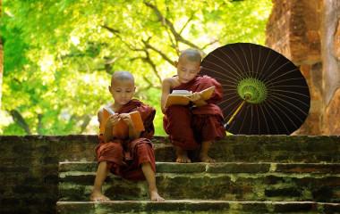 Zwei junge buddhistische Mönche in Myanmar lesen auf der Treppe eines Klosters sitzend