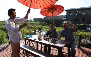 Touristen sitzen auf einer Terrasse von Pfahl-Häusern am Inle-See in Myanmar