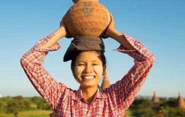 Frau in Myanmar trägt verzierten Tontopf auf Ihrem Kopf und lächelt in die Kamera