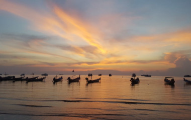 Kanus am Strand von Thailand beim Sonnenuntergang
