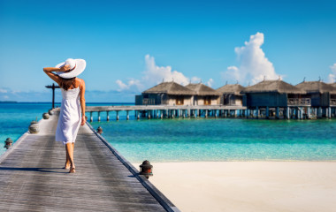Asian couple enjoying romantic luxury lunch setting at tropical beach in Maldives