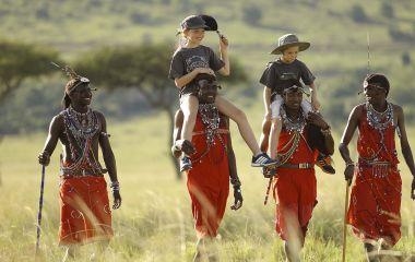 Menschen tragen Kinder auf ihren Schultern
