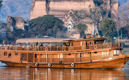 Kreuzfahrtschiff 'Amara Tours' im traditionellen Teakholz-Stil vor felsiger Uferlandschaft in Myanmar