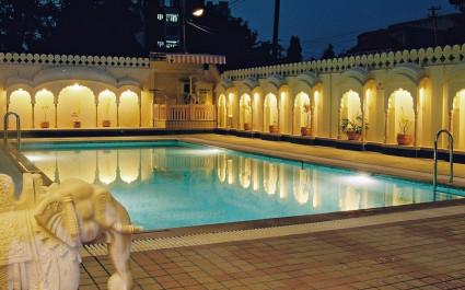 Abendlich beleuchteter Pool im Shahpura House in Jaipur, Nordindien