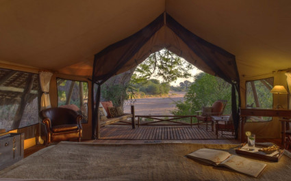 Blick vom Bett aus dem Zelt hinaus in Jongomero in Ruaha, Tansania