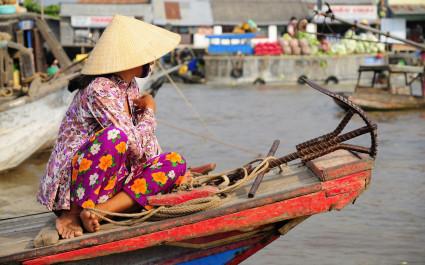 Frau mit Hut sitzt auf Boot im Mekong-Delta, Vietnam