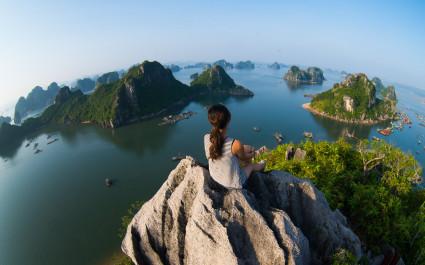 Fisheye-Foto von Frau, die vom Felsgipfel über die Halong-Bucht in Vietnam blickt