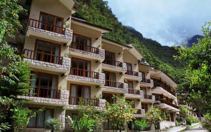 Außenfassade mit Balkonen des Sumaq Machu Picchu Hotels mit Blick auf bewaldeten Berghang in Peru