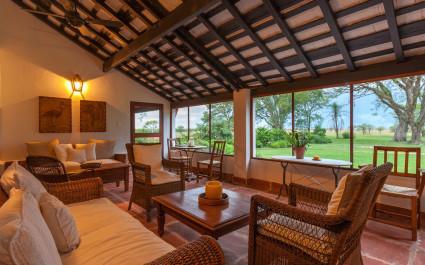 Gemütlicher Wintergarten mit Sofas und großen Fenstern im Hotel 'Rincón del Socorro' in Esteros del Iberá in Argentinien