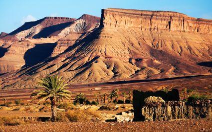 Karge Gebirgslandschaft mit vereinzelten Palmen im Atlasgebirge, Marokko