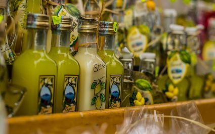 Enchanting Travels Italy Tours Small limoncello bottles for sale in a souvenir shop in Italy; typical Italian souvenir; lemon liquor