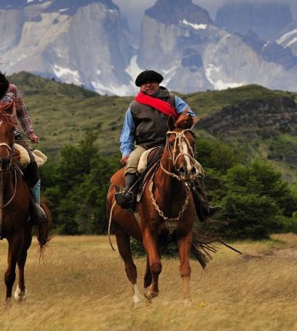 Frau reitet mit Gaucho durch das Gebirge von Patagonien, Argentinien