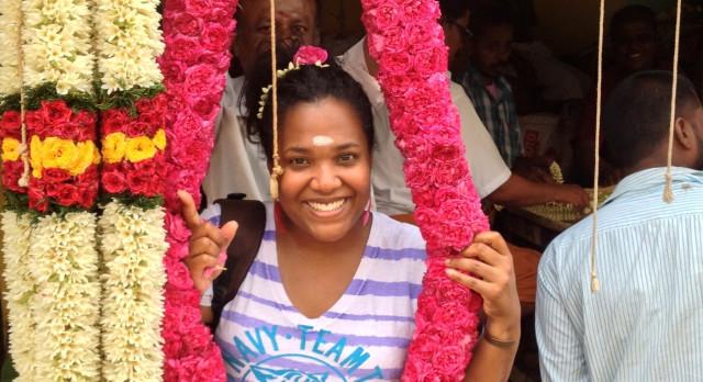 Enchanting Travels Gast Antavia Hamilton neben einer Blumenkette in Indien
